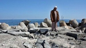 A Libyan man stands on Sirte's bombed fishing harbour 640