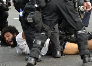 A protester is detained by police at a march and rally during this weekend's NATO summit. (photo: Washington Post)