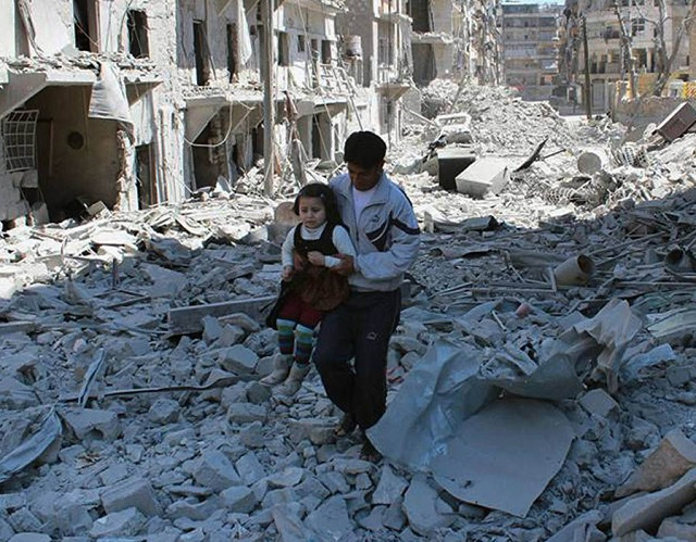 A Syrian man carries a girl amidst the rubble of houses in Aleppo, Syria [Source: AP]