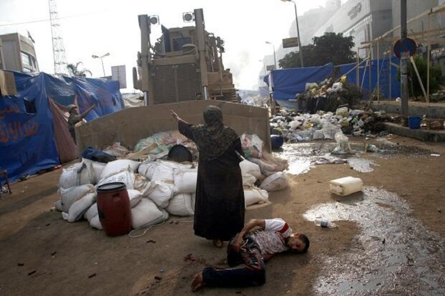 An Egyptian woman stands between a bulldozer and an injured protester bleeding on the ground - Photo - Mohammed Abdel Moneim - AFP - Getty Images