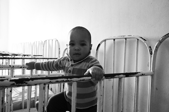 Child swings from side to side in a metal framed cot