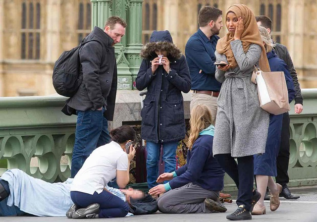 This second photo shows the same woman visibly distressed as she passes the scene of the attack on Westminster Bridge. (Source: Jamie Lorriman/The Guardian)
