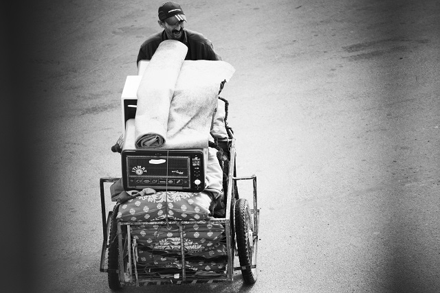 Man carries bedding all his belonging with him