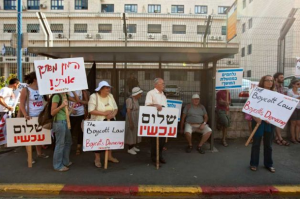 """Israeli left wing activists hold signs as they demonstrate against the suggested boycott law, in front of the Justice ministry in Jerusalem, Sunday, July 10, 2011. The Israeli parliament is bracing for a fiery debate over a bill that allow damage suits against Israelis who call for boycotting West Bank settlements. The signs read in Hebrew: """" Peace Now"""", """" Fighting the Government of Darkness"""", The Right Silent Me"""" . Photo: Sebastian Scheiner / AP"""