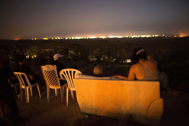 July 12, 2014 - Israeli residents, mostly from Sderot, sit on a hill overlooking the Gaza Strip to watch Israeli bombardment of Gaza. (By Menahem Kahana/AFP/Getty Images)