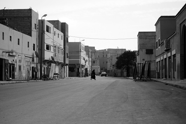 Woman crosses the street in a deserted part of La'ayoune
