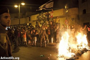 "The mob setting garbage on fire and singing ""The people wants the Africans to be burned"" after a protest against African refugees and asylum seekers in Tel Aviv's Hatikva neighborhood on May 23, 2012. (Photo: Activestills)"