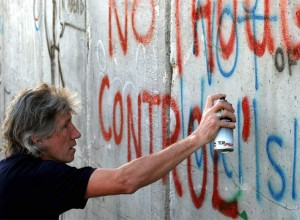 "British rock musician and Pink Floyd co-founder Roger Waters spray-paints the words ""No thought control"" on Israel's West Bank separation barrier in Bethlehem. (Photo: AP)"